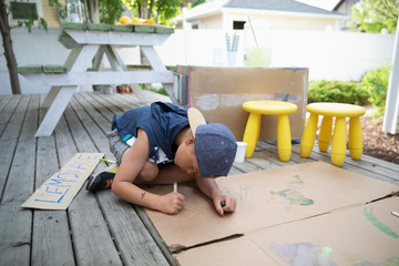 Boy drawing on cardboard, making lemonade stand