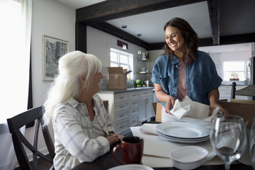 Smiling daughter helping senior mother downsize, packing dishes