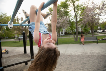 Playful girl hanging upside down from monkey bars at playground