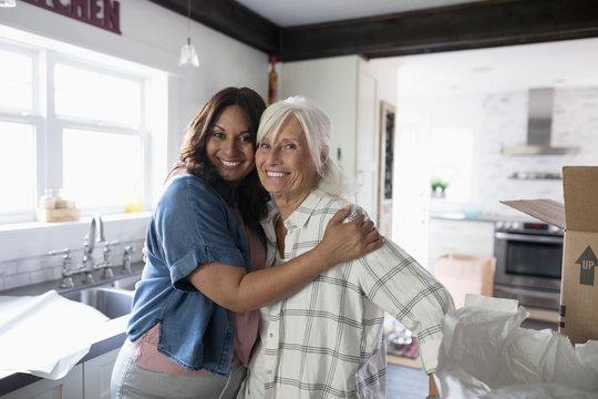 Portrait affectionate daughter hugging senior mother, helping downsize