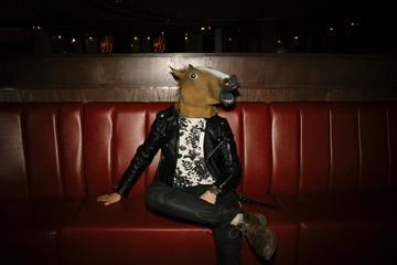 Portrait playful, humorous male millennial wearing horse head in nightclub