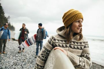 Woman enjoying weekend surfing getaway with friends, carrying surfboard on rugged beach