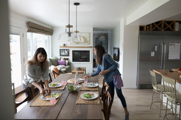 Mother and tween daughter setting the table