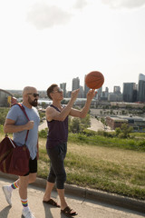 Gay male couple with basketball on sunny urban street
