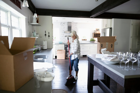 Senior woman downsizing, packing and sweeping kitchen