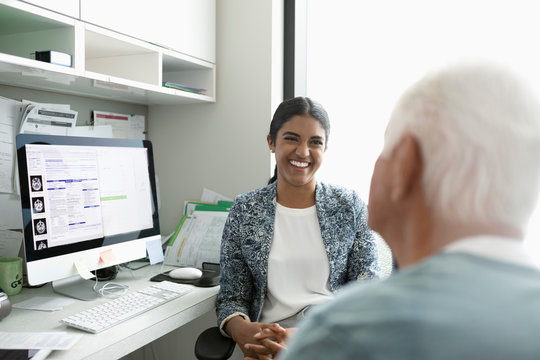 Laughing female doctor talking with senior male patient in clinic office