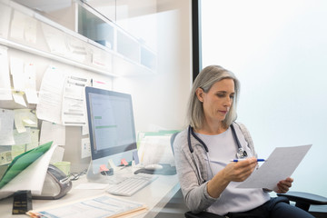 Female doctor reviewing paperwork in clinic office