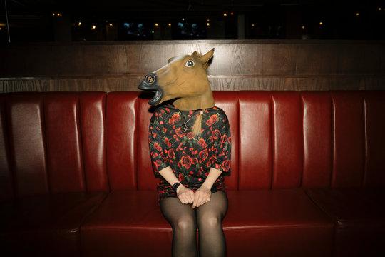 Portrait female millennial wearing horse head in nightclub