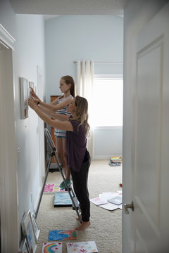 Mother and daughter hanging artwork in bedroom