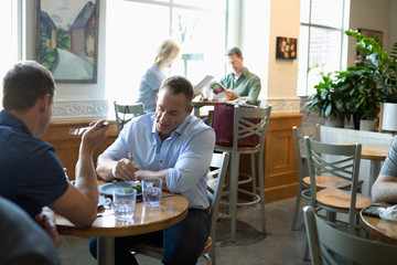Male gay couple eating lunch in cafe