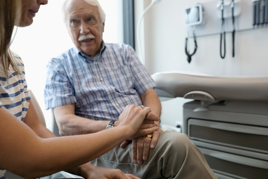 Caring daughter comforting senior father waiting in clinic exam room