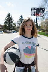 Portrait confident, cool tween girl playing basketball