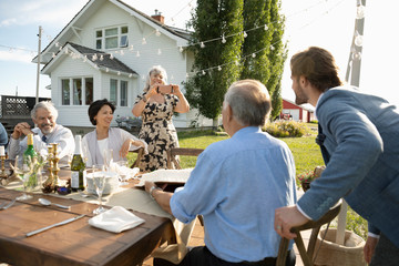 Woman photographing father and son at retirement party table