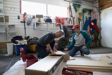 Father and son assembling flat pack furniture in garage