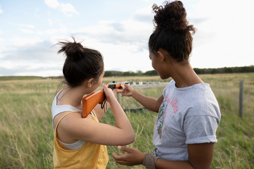 Teenage girl friends with rifle shooting cans in field