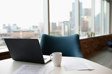 Laptop, paperwork and coffee cup on table in highrise office Fotobehang
