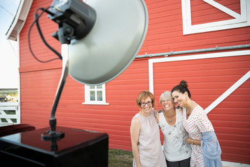 Playful women friends enjoying wedding photo booth in front of red barn