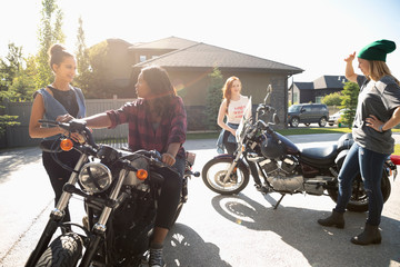 Young women friends with motorcycles in sunny driveway