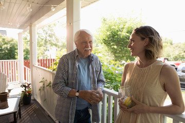 Senior father and daughter drinking lemonade and talking on porch