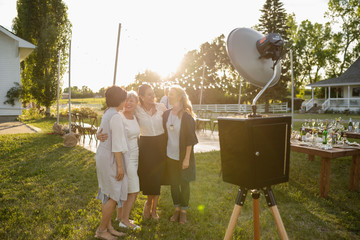 Women friends posing at photo booth at wedding party in sunny rural garden