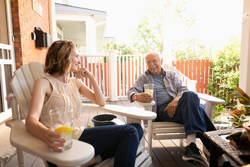 Daughter and senior father drinking lemonade and talking on summer porch
