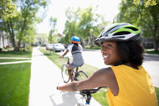 Smiling tween girl in helmet bike riding on sunny neighborhood sidewalk