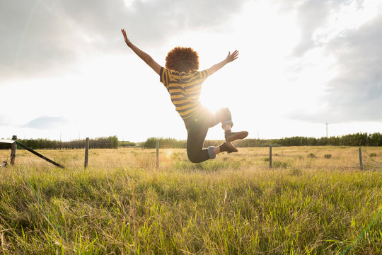 Playful teenage girl jumping for joy in sunny rural field
