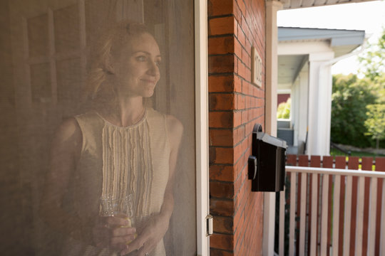Serene woman standing at porch screen