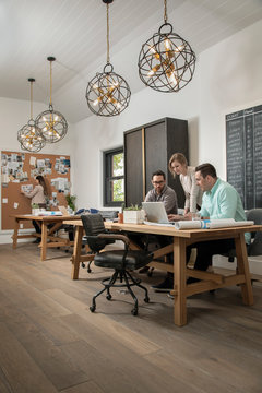Home builder architects planning at laptop in office