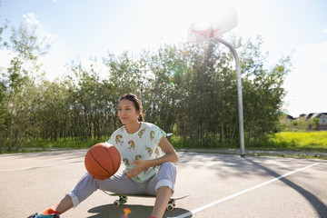 Young woman with basketball on skateboard at park basketball court