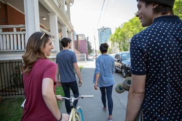 Millennial friends with skateboard and bicycle walking on neighborhood sidewalk