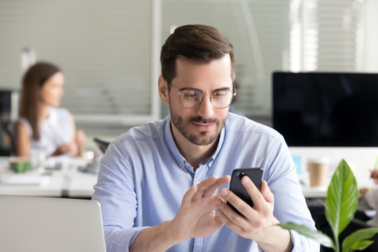 Male employee using smartphone reading news at work