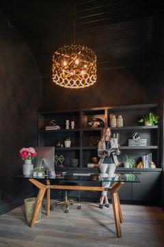 Female designer working in dark, creative office