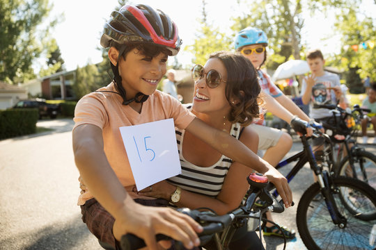 Happy mother and son preparing for bike race at summer neighborhood block party
