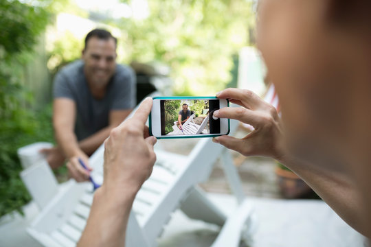 Gay man with camera phone photographing partner painting patio furniture