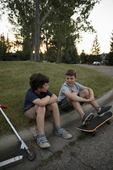 Boys with scooter and skateboard on curb at park