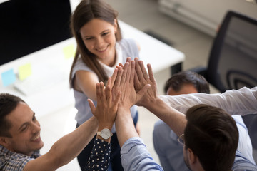 Close up of coworkers give high five motivated for success