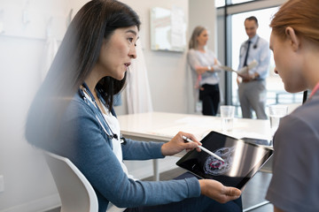 Female doctor and nurse discussing brain scan x-ray on digital tablet in clinic meeting