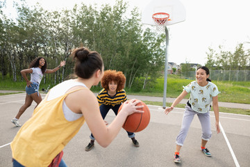 Teenage girl friends playing basketball at park basketball court