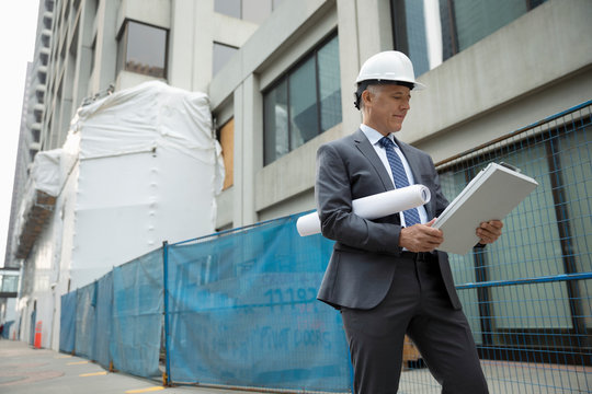 Male architect with blueprint and clipboard walking on urban sidewalk