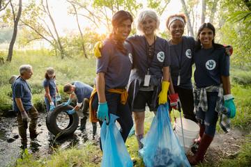 Portrait smiling women volunteering, cleaning up garbage in park