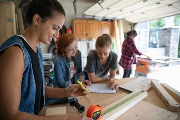 Young women friends woodworking in garage