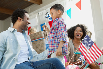 Happy family with American flag celebrating Independence Day at home
