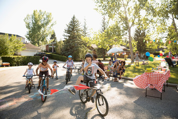 Kids enjoying bike race at summer neighborhood block party Fototapete