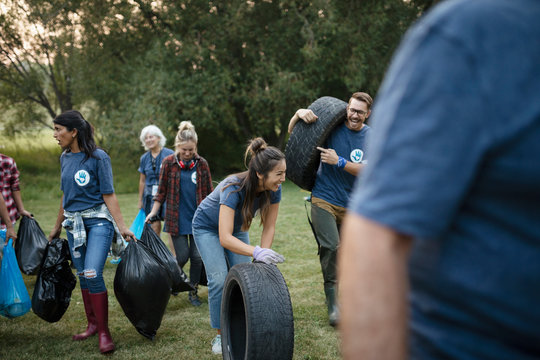 People volunteering, cleaning up garbage in park and rolling tires