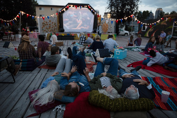 Crowd relaxing, enjoying movie in the park