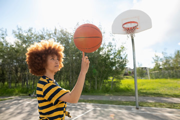 Cool teenage girl with afro balancing basketball on finger at park basketball court