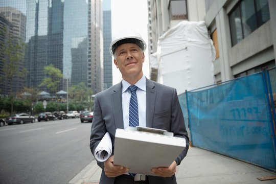Portrait confident male architect with blueprints and clipboard on city sidewalk