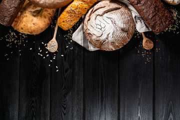 Bakery - gold rustic crusty loaves of bread on black chalkboard background. Still life captured...