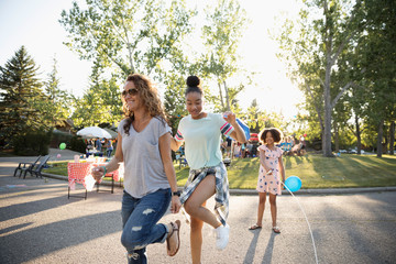 Mother and daughters jump roping at summer neighborhood block party in street